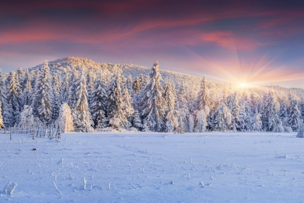 Nace el sol detrás de las montañas e ilumina el paisaje nevado