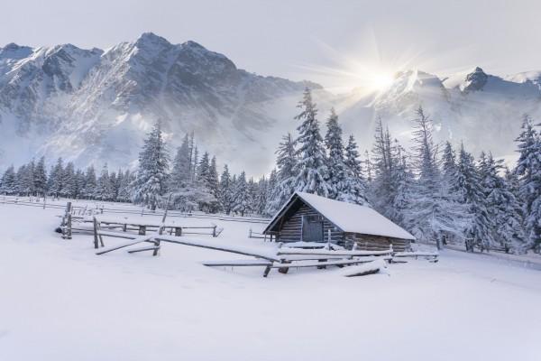 Cabaña cubierta de nieve recibiendo los rayos del sol