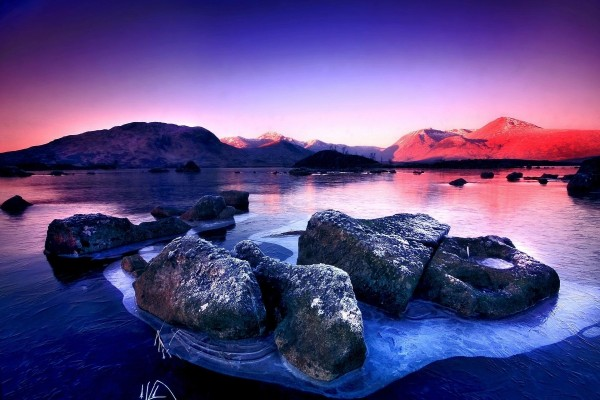 Lago congelado con reflejos azules y rojos del amanecer