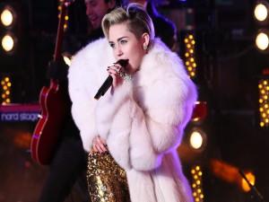 Miley Cyrus en un concierto con un bonito abrigo blanco