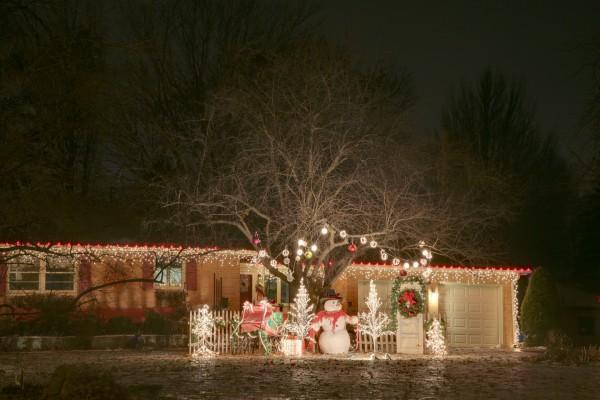 Muñeco de nieve y luces decorando una casa en Navidad