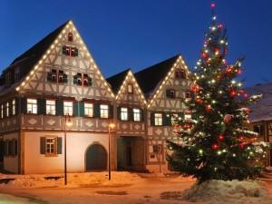 Postal: Árbol de Navidad iluminado frente a una hermosa casa