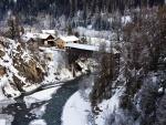 Nieva sobre un río junto al pueblo