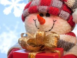 Postal: Muñeco de nieve con un regalo para Navidad