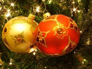Postal: Una bola naranja y otra amarilla decorando el árbol de Navidad