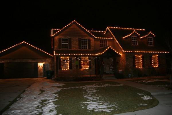 Jardín nevado y luces de Navidad en la casa