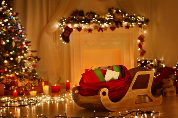 Regalos sobre un trineo de madera junto a un árbol de Navidad