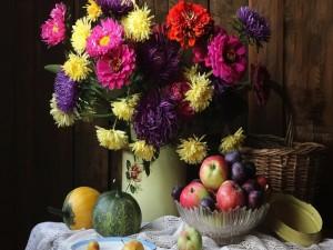Flores en un recipiente junto a unas frutas