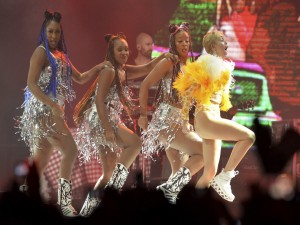 Miley Cyrus y tres bailarinas sobre el escenario