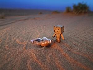 Postal: Danbo junto a una botella sobre la arena