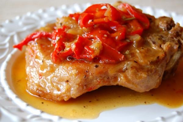 Pimientos sobre una pieza de carne en salsa