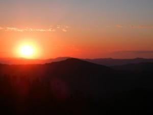 El sol brillando al atardecer sobre las montañas