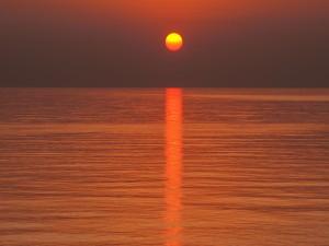 Postal: El sol proyectando luz sobre el agua