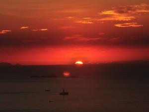 El sol tras las nubes oscureciendo el mar