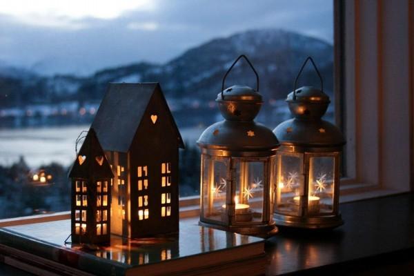 Magníficos faroles con velas encendidas junto a la ventana