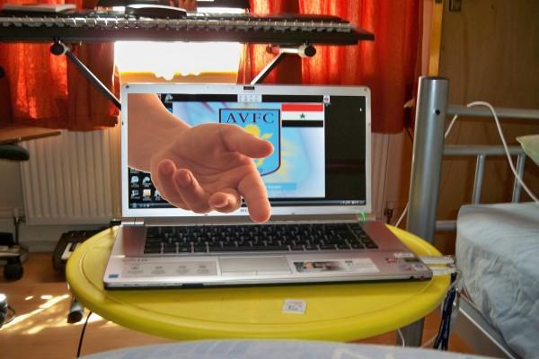 Mano amiga saliendo de la pantalla de un portátil