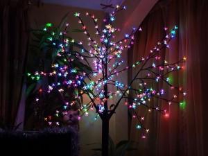 Postal: Un árbol con luces de colores encendidas en Navidad