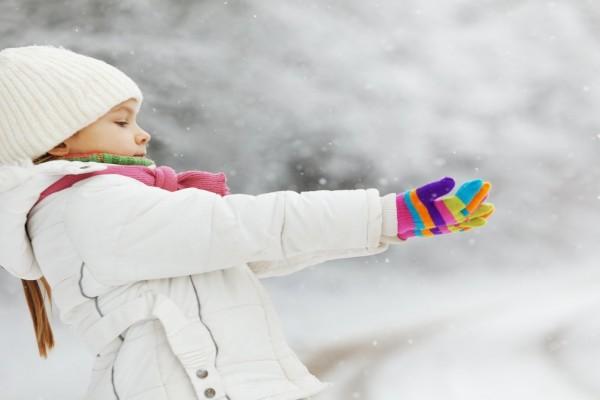Niña muy abrigada en un día frío de nieve