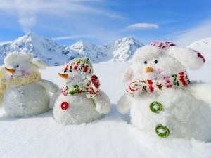 Tres simpáticos muñecos de nieve en la montaña