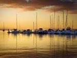 Barcos reflejados en el agua al caer la tarde