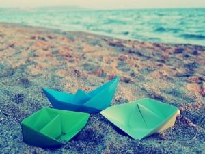 Postal: Barcos de papel sobre la arena de una playa