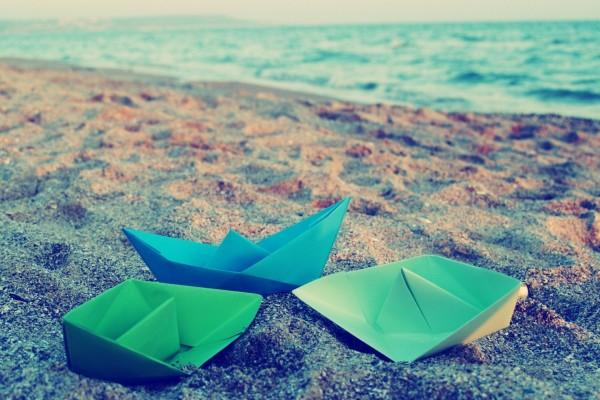 Barcos de papel sobre la arena de una playa
