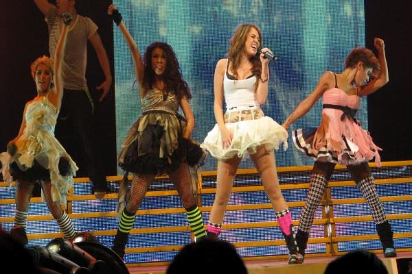 Miley Cyrus y bailarinas en un concierto