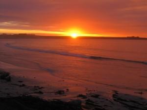 Postal: Admirando el atardecer junto a la orilla del mar