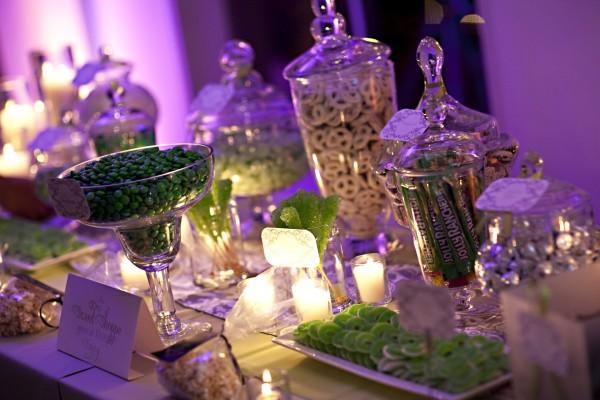 Botes y platos con caramelos verdes entre velas