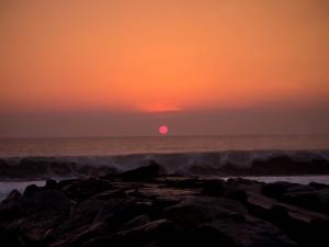 Vista del sol al anochecer en una playa rocosa
