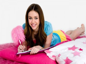 Una joven Miley Cyrus escribiendo en un diario