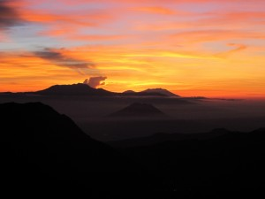 Postal: Cielo con bonitos colores al amanecer sobre unas montañas