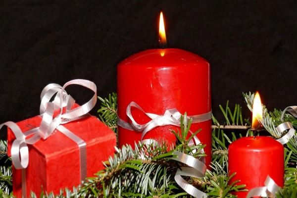 Regalo y velas rojas sobre ramas de pino para decorar en Navidad