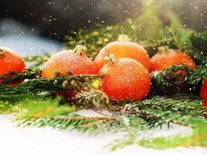 Bolas naranjas cubiertas de copos de nieve en Navidad