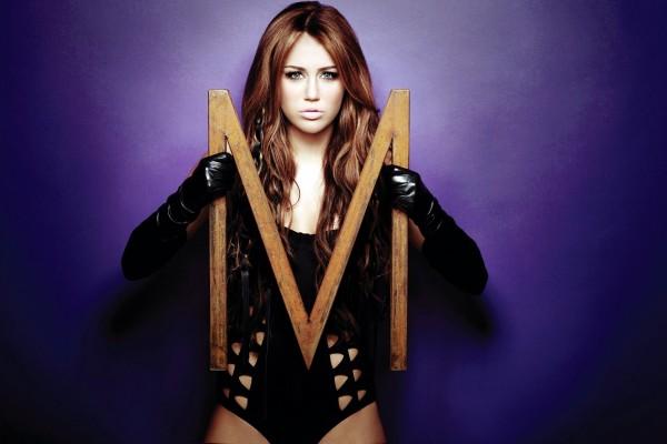 Miley Cyrus sosteniendo la inicial de su nombre