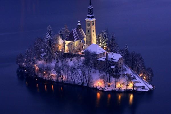 Iglesia iluminada en una isla cubierta de nieve