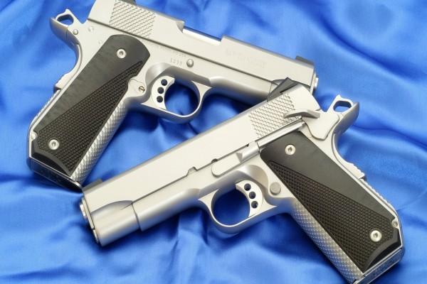Dos pistolas plateadas sobre una sábana azul