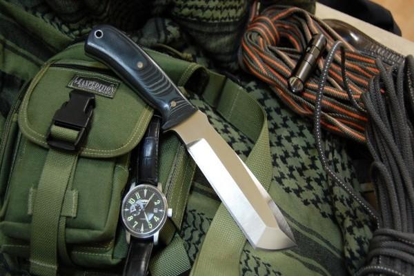 Cuchillo, linterna y reloj sobre un bolso
