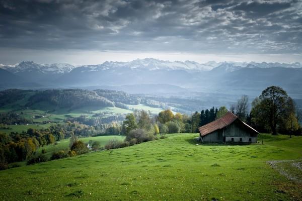 Cabaña en un verde valle con vistas a las montañas