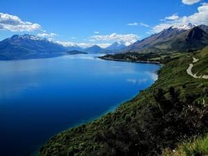 Postal: Un gran lago rodeado de montañas