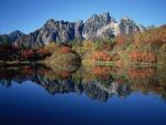 Árboles otoñales y montañas reflejados en el lago