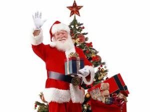 Santa Claus saludando junto al árbol de Navidad