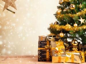 Regalos con cintas doradas junto a un árbol de Navidad