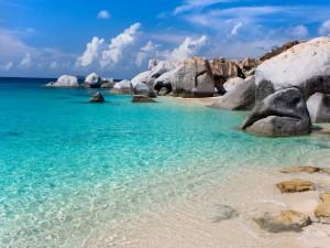 Postal: Grandes rocas en una playa de agua azul
