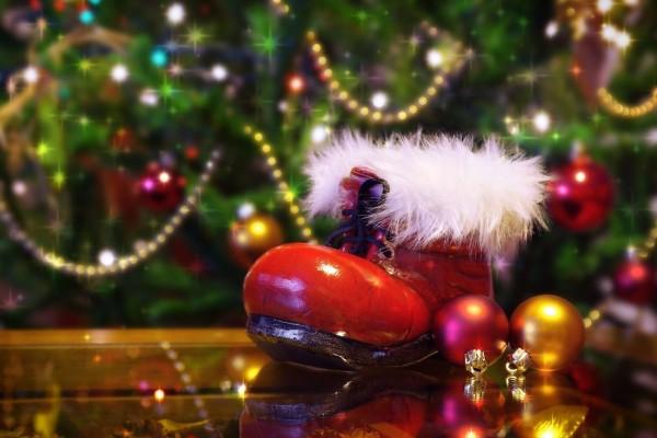 Bota de Santa Claus junto al árbol de Navidad iluminado