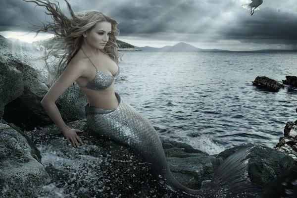Sirena sentada en las rocas junto al mar
