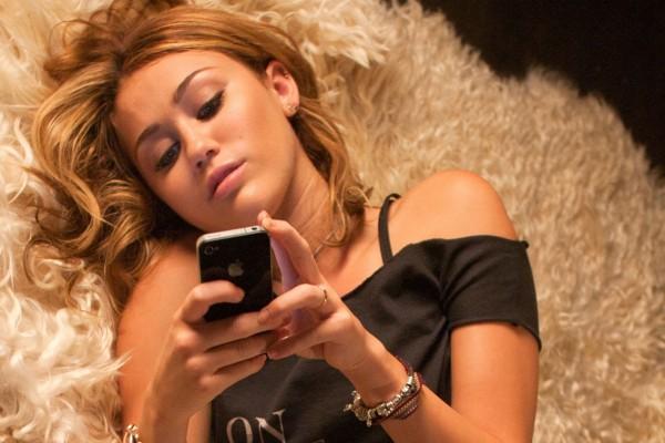 La cantante y actriz Miley Cyrus mirando su móvil