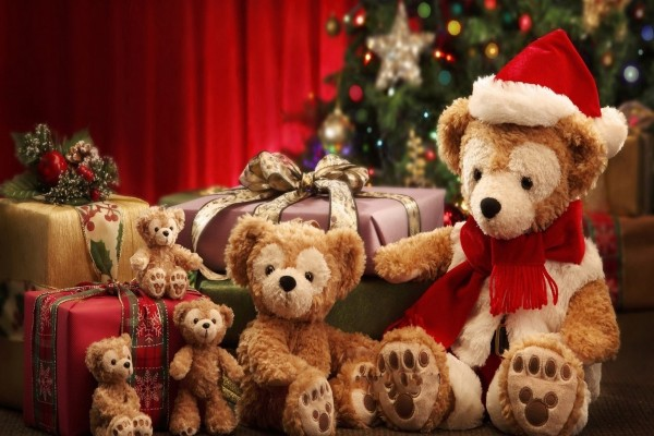 Una familia de osos de peluches junto al árbol de Navidad