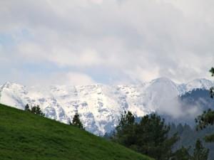 Postal: Nubes entre las montañas nevadas
