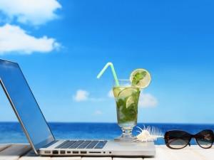 Refresco y gafas para trabajar con un portátil en vacaciones